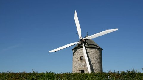 an old windmill in the countryside of Moidrey, Normandy, France.   A windmill is a mill that converts the energy of wind into rotational energy by means of vanes called sails or blades.