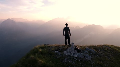 Aerial - Flying around young man standing victoriously on top of the mountain at sunset
