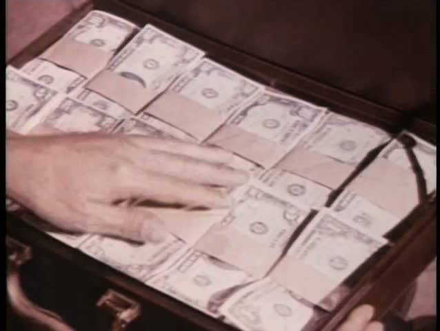 Close-up hand touching money in suitcase