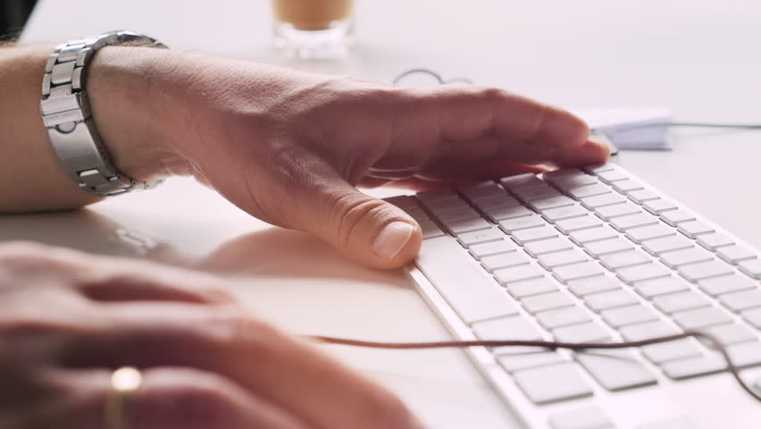 Left hand of man is sitting on a keyboard why is his right hand is using a mouse. White desk in modern office. | Shutterstock HD Video #18420466