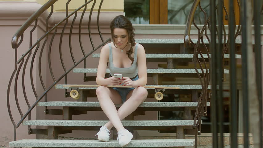 4K CINEMAGRAPH - motion photo seamless loop - Hipster girl sitting on the stairs with a longboard skateboard and listening to music on the phone through earphones. 60 FPS 4K UHD | Shutterstock HD Video #18432856