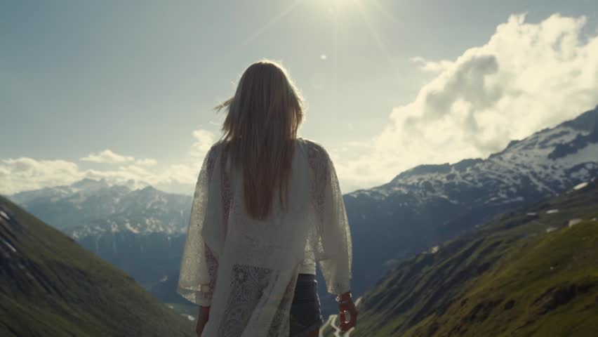 The athletic girl is standing on the top of the mountains. She raises her hands to the Sun, shots stabilizer, slow motion. Action, energy and yoga exercise
