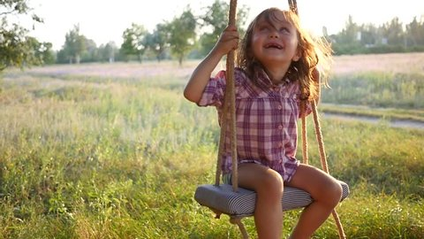 Happy cute little child girl have fun sway spin on a swing on nature sunset