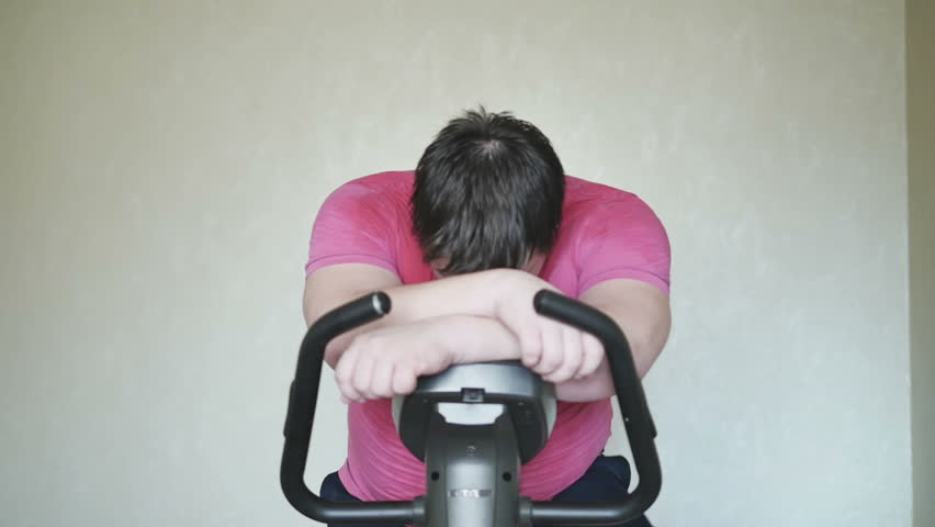 Overweight men survived on a exercise bicycle, and happy about it | Shutterstock HD Video #18455956