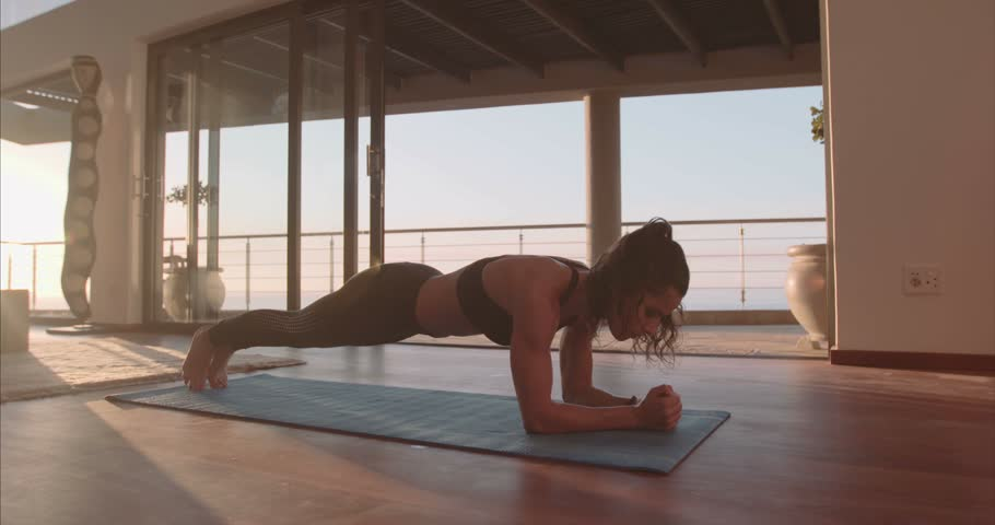 Fitness female doing stretching workout on exercise mat at home. Young woman exercising on fitness mat in living room.