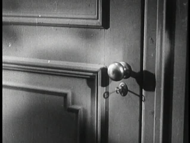 Low angle view of man entering door and locking behind him
