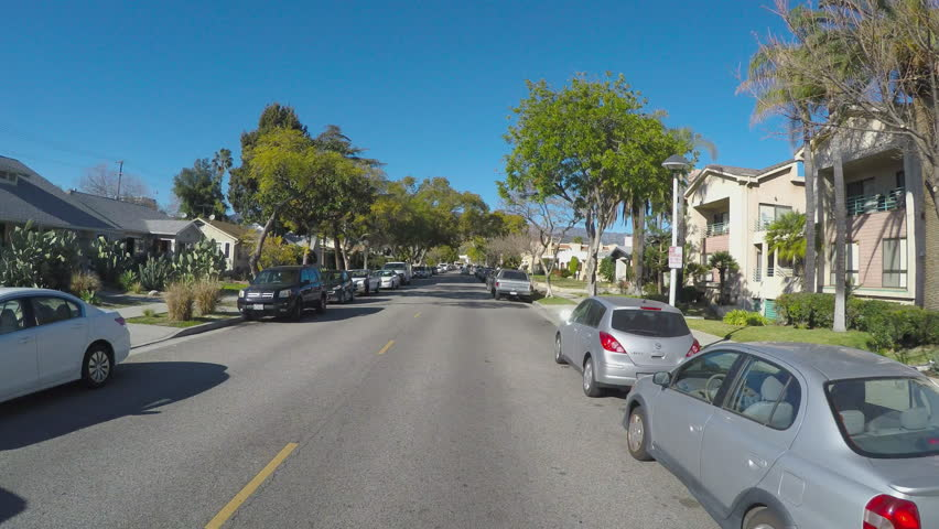 GLENDALE, CA/USA: February 21, 2016- Point of view driving vehicle shot through a residential neighborhood street. The vehicle passes by apartments and homes in a suburban part of town.