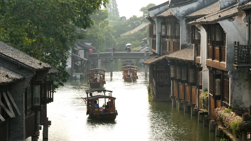 Wuzhen historical canal village, China - high angle telephoto view of canal reflecting sky, with wooden barges with old housing terraces ether side & distant bridge with people crossing & rural trees 2016