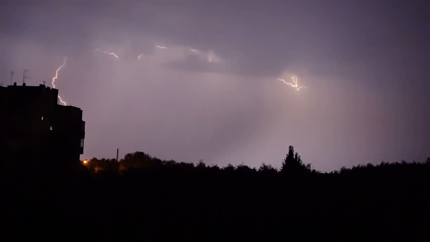 Severe thunderstorm breaks in city, striking lightning bolts in dark night sky. Vicious rainstorm with electric bolts and thunder clashes at night