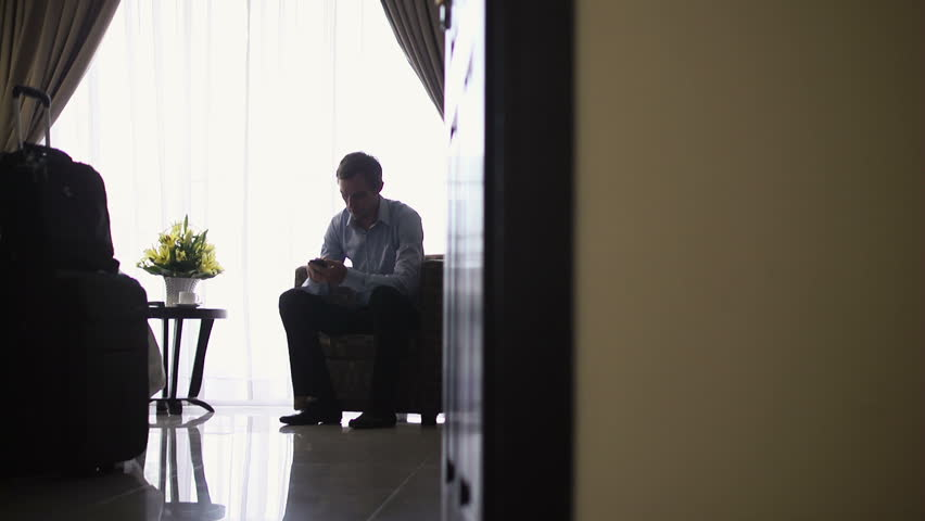 White collar worker talking with mobile telephone in hotel room during business trip. Dolly shot