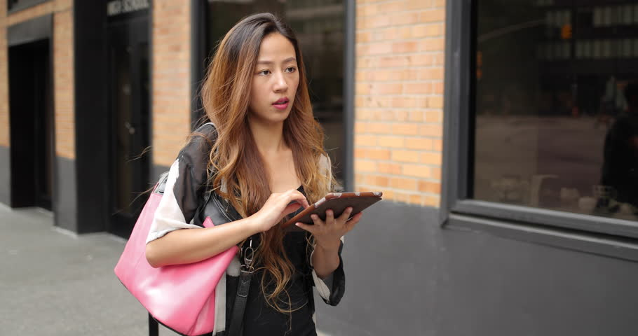 Young Asian woman in city walking street using tablet | Shutterstock HD Video #18633842