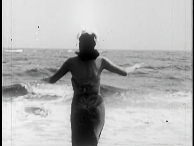 Rear view of woman walking into ocean
