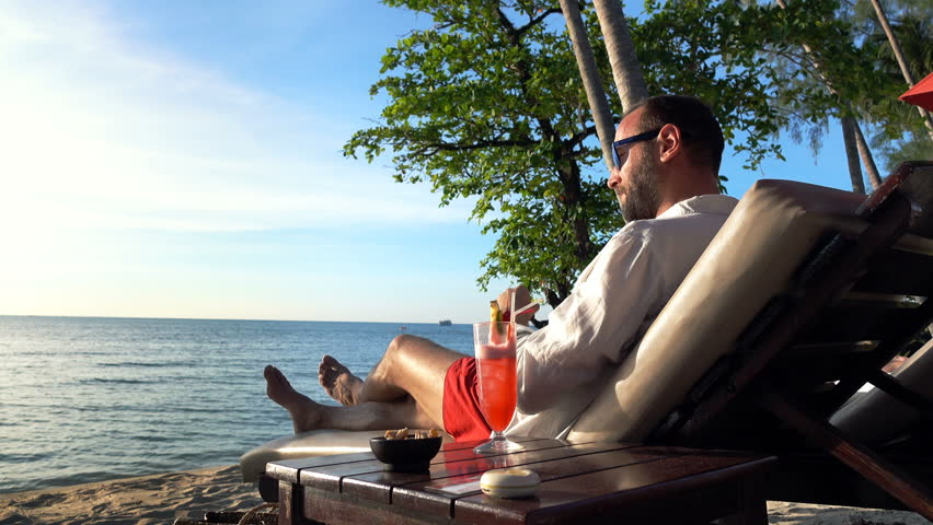 Happy man raising toast with cocktail to camera lying on sunbed on beach