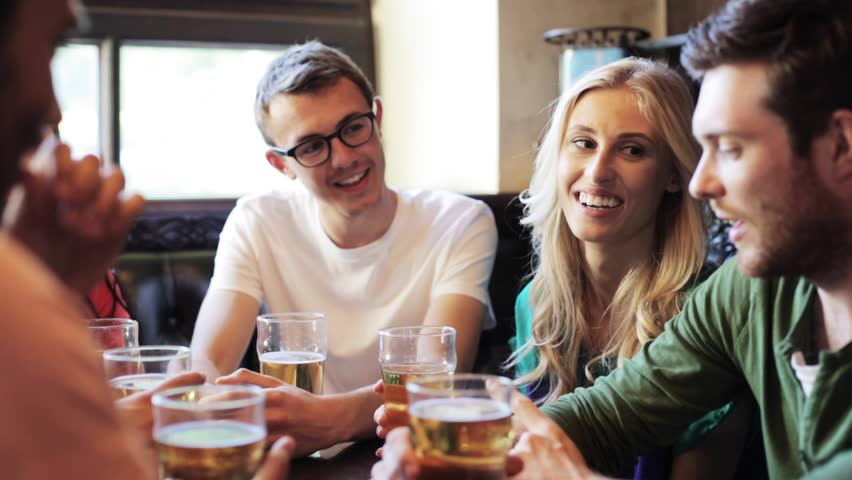 People, leisure, friendship and communication concept - happy friends drinking beer and talking at bar or pub | Shutterstock HD Video #18645116