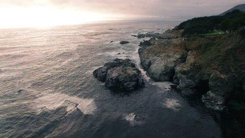 4k aerial along waves splashing rocks
