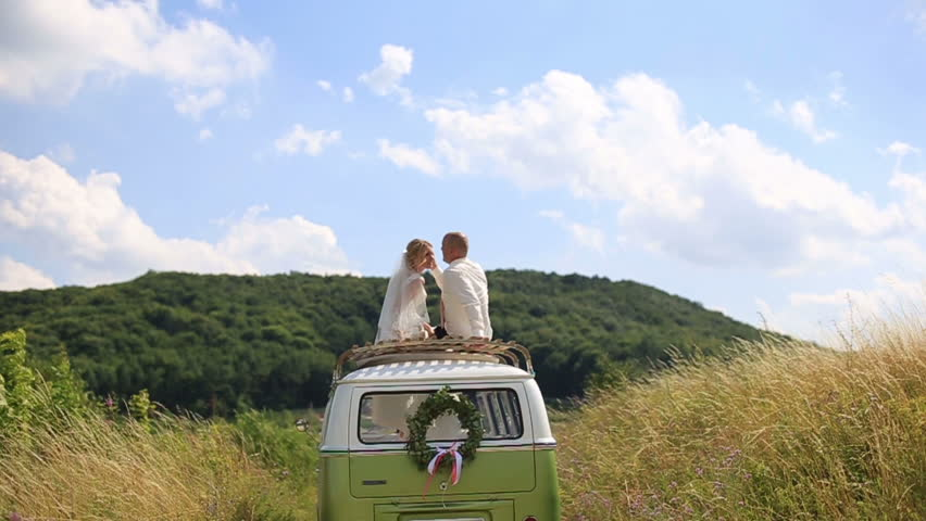 Happy young newlyweds bride and groom on the top of rerto wedding bus in the sunny summer field. Tender moment of love