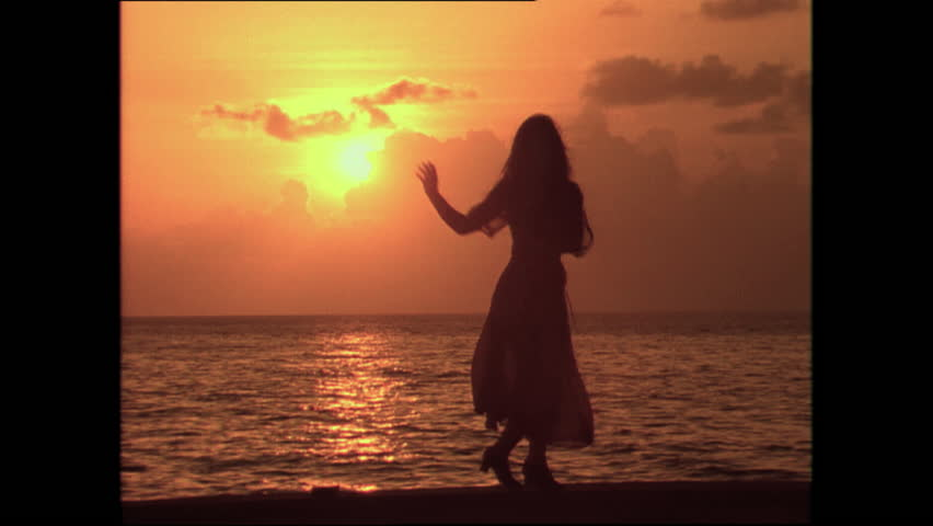 A sexy woman dances in front of the sunset in a Latin American country Cuba in the 1980s. (Cuba 1980s)