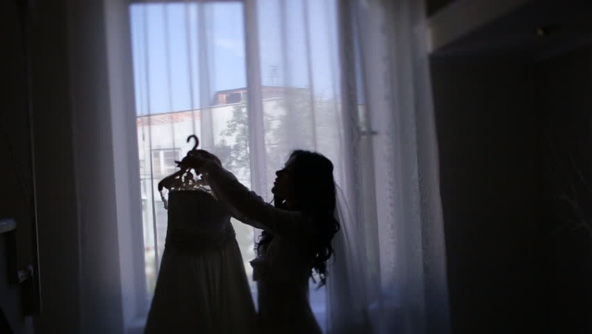 Happy bride in white lace robe holding her wedding lace dress standing by the window | Shutterstock HD Video #18714086