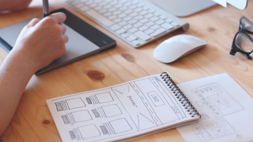 A web designer works on the graphics tablet, the site layout drawn with sketch book.