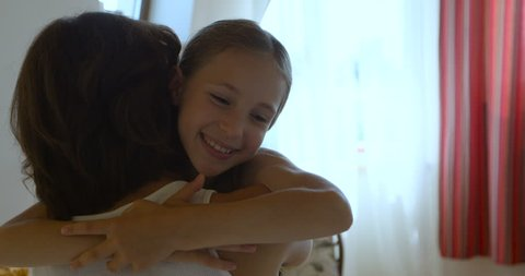 Smiling daughter rushes into mother's arms at home and gives her a big hug.