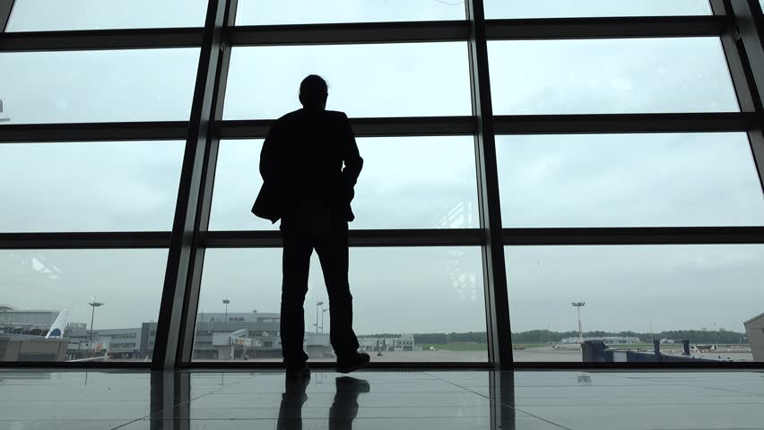 Man come and stand at full height, gaze out airport terminal window, silhouette view. Empty aeroport field outside, hipster person look out while waiting for boarding gate open, VKO lounge hall   Shutterstock HD Video #18761387