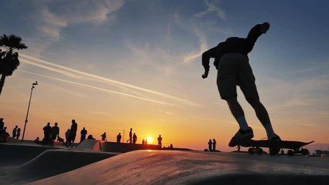 Silhouette of skater on skateboard jumping over sunset sky at Venice Beach skate park, California. Slow motion.