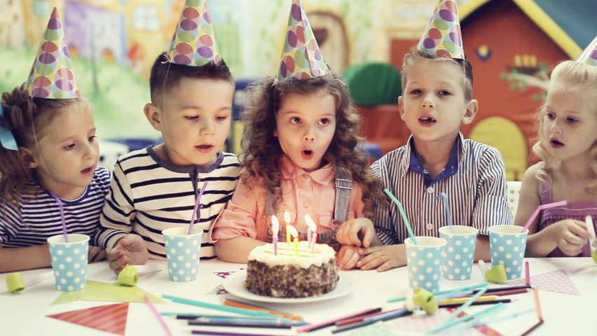 children blowing out candles on birthday cake