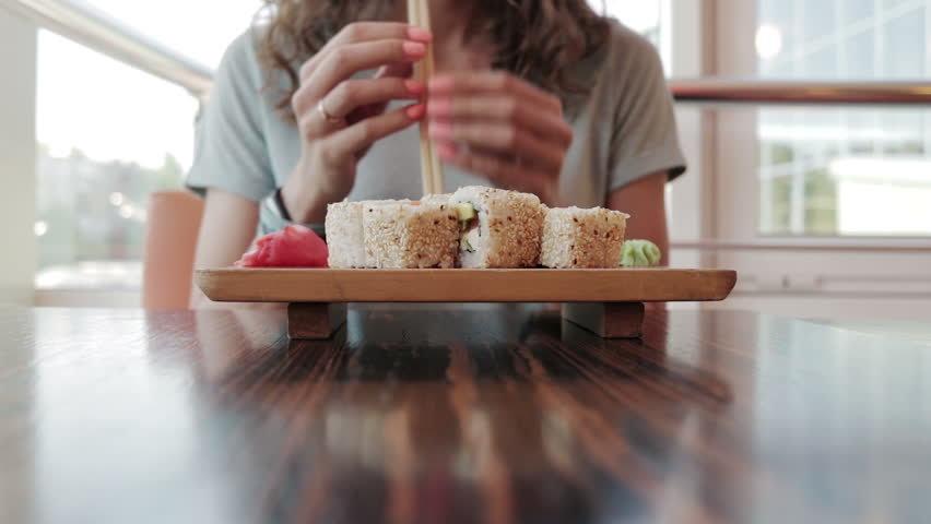 Young woman in cafe eating sushi with chopsticks