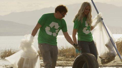 Medium panning shot of volunteers carrying garbage from lake / Vineyard, Utah, United States