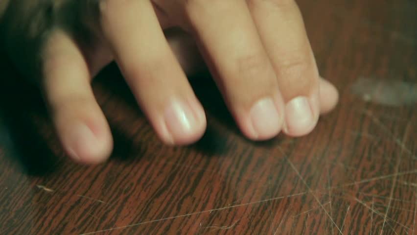 Man knocks fingers on the table. Makes rhythmic beats.