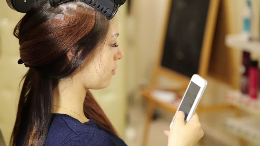 Young woman in a beauty salon, hairdresser doing hairstyle to beautiful model. customer talking on the phone | Shutterstock HD Video #18875456