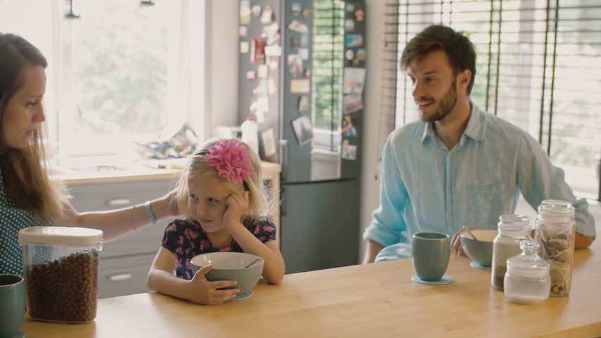 Young mother and father are smiling at their daughter who is having cereal for breakfast. Slow mo, Steadicam shot