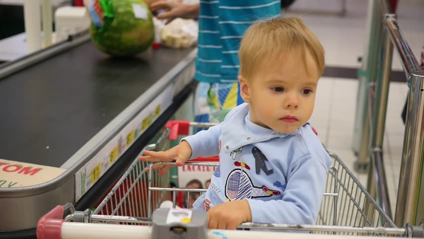 The child sits in the shopping cart in the store | Shutterstock HD Video #18919952
