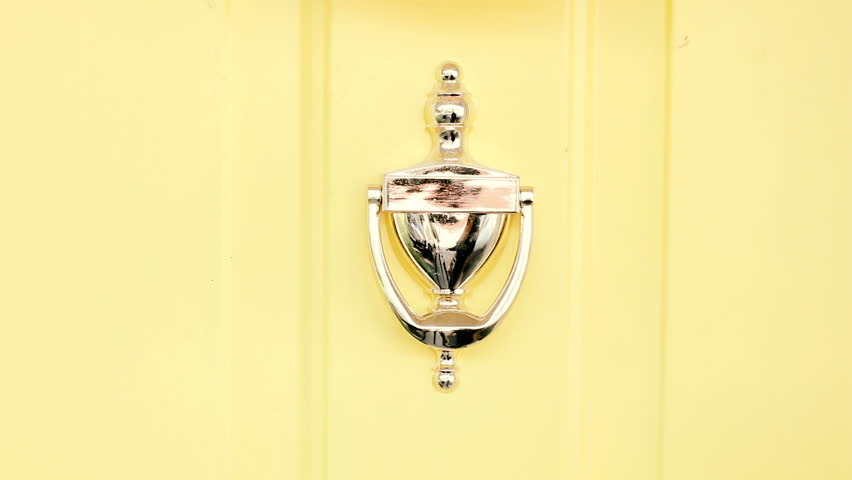 Classic door knocker on yellow home entrance