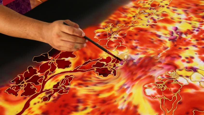 An artist carefully paint the flower motif on a reddish batik fabric with tiger-like pattern