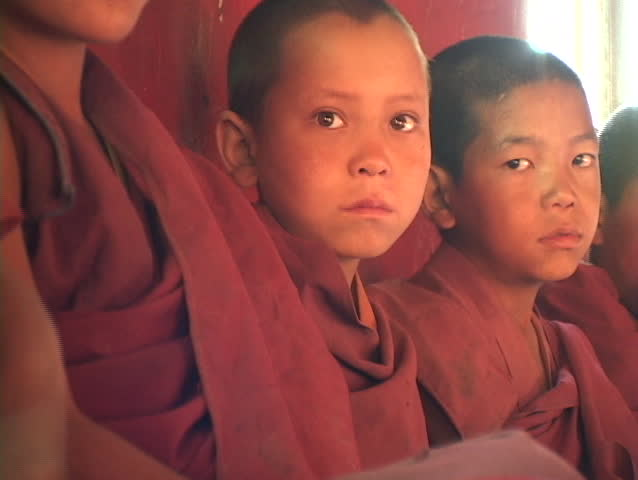 Buddhist boys sit in a row.