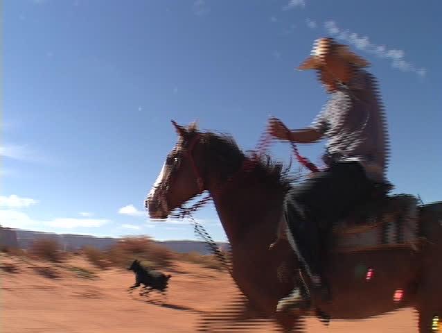 A cowboy on horseback rides fast across the Utah desert.