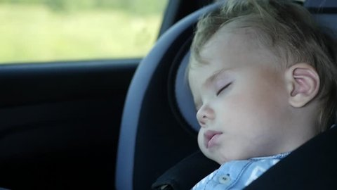 The baby sleeps in the car in the way. Sleeping child at back chair in car in slow motion.