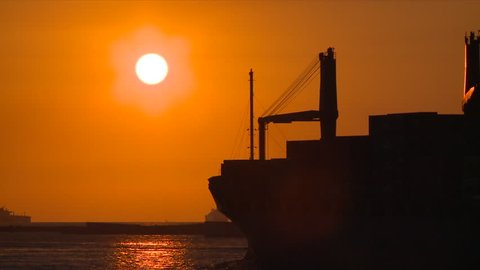 A ship is sailing near the port of Kaohsiung, the largest harbor in Taiwan. It is sunset.