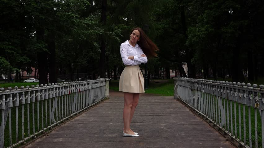 Young proud woman in short skirt turn back, slow motion shot. Girl in haughty mood cross arms on breast, look straight to camera, full height portrait. Old empty footbridge in dark city park