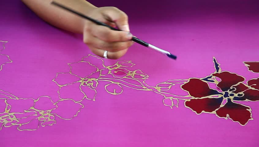 An artist carefully paint the flower motif on a pink batik fabric