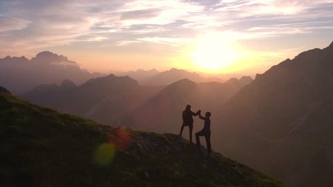 Aerial - Silhouette of a couple giving each other a high five celebrating successful climb on the mountain in beautiful sunset