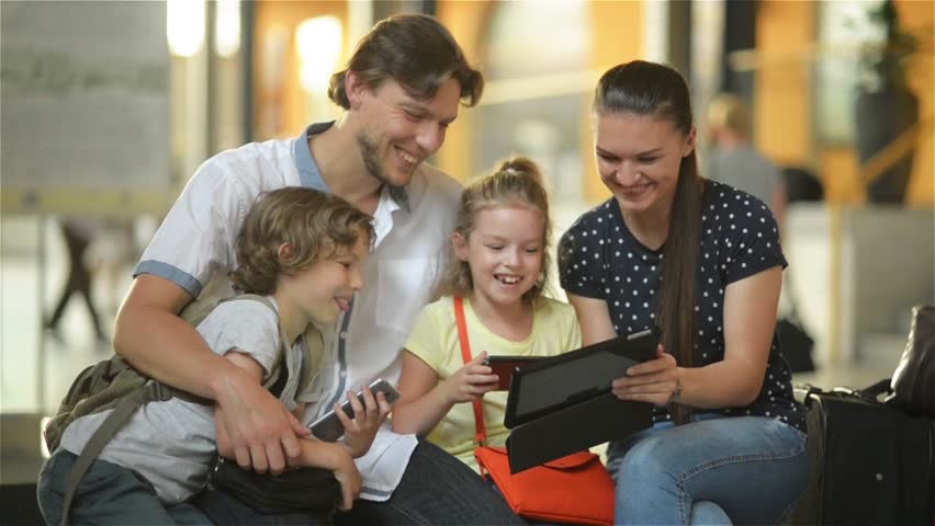 Young mother showing to her family something interesting in tablet PC while they are sitting in airport departure lounge or railway station. | Shutterstock HD Video #18966436