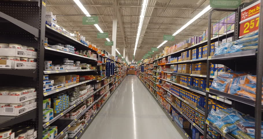 MONTREAL, CANADA - AUGUST 2016: Shopping Inside Walmart - Professional Steadicam Shot (Aisle with canned food, dry snacks, baking flour etc.)
