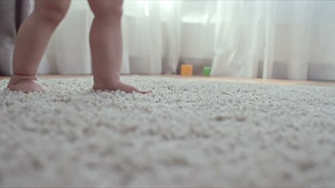 Closeup of tiny barefoot legs of baby walking on the soft rug without any help