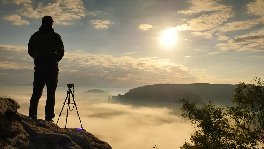Photographer in green windcheater and black trekking trousers stay camera on tripod at cliff edge. Dreamy fogy landscape, blue misty sunrise in a beautiful valley below | Shutterstock HD Video #18983296