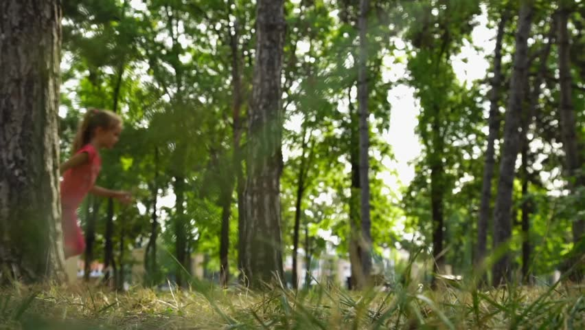 Girl running in the park among the trees. Defocused shooting. | Shutterstock HD Video #18987556