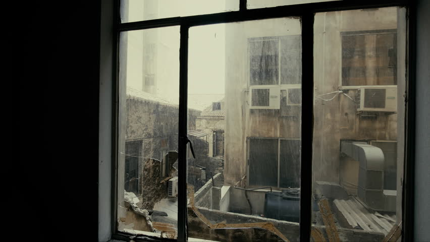 4K Window view at collapsed, half-ruined buildings in ghetto city block.Almost collapsed and ruined city block as witnessed from the broken windows of a near apartment building.Tracking gimbal motion.