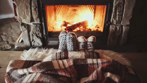 Couple Feet in Wool Socks by the Cozy Fireplace, 4K. Man and Woman sitting under the blanket, relax by warm fire and warming up their feet. Close up. Winter and Christmas holidays concept.