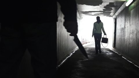 Silhouette of a man carry a knife follows a young woman in a dark tunnel. Violence against women concept. Real people, copy space